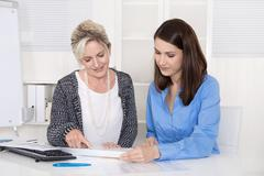 Two attractive businesswoman in meeting analyzing budget. Stock Photos