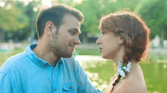 Young couple in love talking and kissing in front of a romantic lake Stock Footage