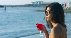 Beautiful young woman drinking cocktail by the sea: sunset, wind, summer, 4k Stock Footage