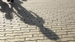 Moving shadows and legs of walking children on sunset flag-stone pavement Stock Footage