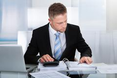 Hardworking businessman analysing a report Stock Photos