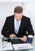 Stylish hardworking businessman using a tablet computer at his desk concentra Stock Photos
