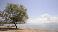 Lake Prespa Macedonia shore still weather sunny tree chairs flowing water Stock Footage