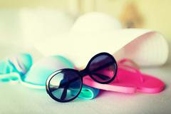 Bikini top, hat, flip-flop and sunglasses Stock Photos