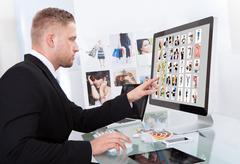 Businessman editing photographs Stock Photos