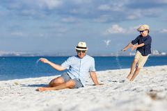 Happy father and his son having fun at the beach Stock Photos