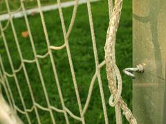 Hang bended soccer nets, soccer football net. Playground in the background - stock photo