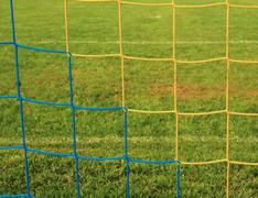 Hang bended soccer nets, soccer football net. Green grass  in background - stock photo