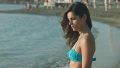 Beautiful young woman standing by the sea relaxing in the sun: wind, summer, 4k Arkistovideo