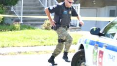 4K UHD - Officer running in peaceful neighborhood with hand on his gun Stock Footage