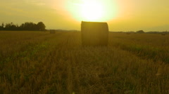 AERIAL: Flying over hay bale on field at sunset - stock footage
