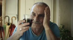 Alone and sad old man taste a glass of red wine: alcohol, depression, 4k Stock Footage