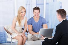 financial advisor explaining investment plan to young couple on laptop in off - stock photo