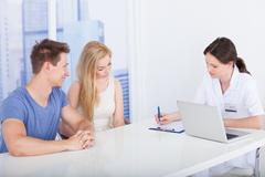 female doctor discussing report with young couple at desk in clinic - stock photo
