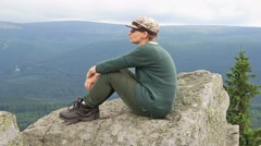 Pensive woman resting on a cliff during a mountain trip Stock Footage