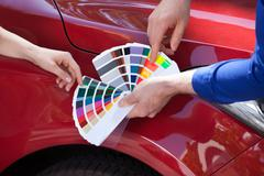 Cropped image of mechanic showing color samples to customer against car Stock Photos