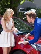 Stock Photo of cropped image of mechanic showing color samples to customer against car