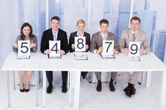 portrait of confident business people showing score cards - stock photo