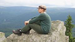 Woman rest on a mountain peak during a hiking trip Stock Footage