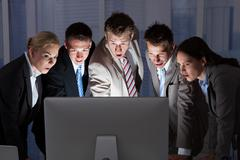 Surprised young business people looking at computer monitor in office Stock Photos