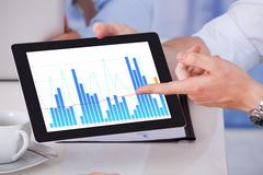 Cropped image of businessman showing graph on digital tablet to colleagues in Stock Photos