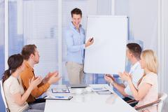 Young business people clapping for male colleague after presentation in offic Stock Photos