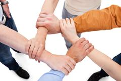 Cropped image of young friends linking hands in team over white background Stock Photos