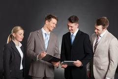 Happy business people discussing over clipboard while standing against black  Stock Photos