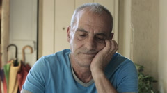 elder man is sitting alone at the table thinking to his problems: sadness, sad - stock footage