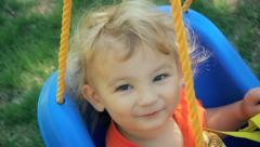 Cute little blond boy on child swing in backyard in summer Stock Footage