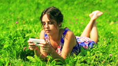 Happy girl in blue dress lying on green meadow and typing on cellphone Stock Footage