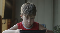 Cute boy using tablet computer: internet, games, fun, learning Stock Footage