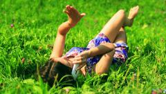 Girl lying on green meadow and talking on cellphone - stock footage
