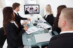 businesspeople attending video conference at desk in office - stock photo