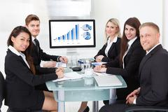 Portrait of confident business team sitting at desk in office Stock Photos