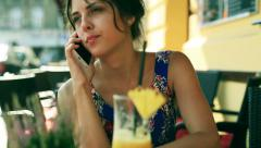 Unhappy girl talking on cellphone and sitting in the street cafe Stock Footage