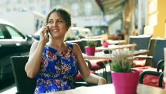 Pretty girl in beautiful dress sitting in street cafe and chatting on cellphone Stock Footage