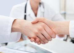 cropped image of doctors shaking hands at desk in clinic - stock photo