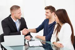 Smiling financial advisor shaking hand with couple at office desk Stock Photos