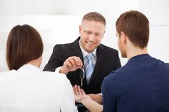 Happy agent giving car key to couple in office Stock Photos