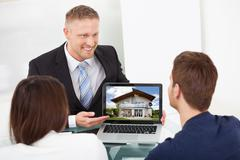smiling advisor showing house picture to couple on laptop at office desk - stock photo