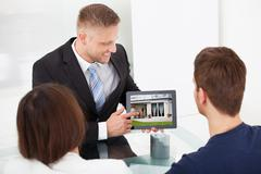 Smiling advisor showing house picture to couple on tablet at office desk Stock Photos