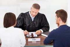 rear view of couple with judge writing at desk in court - stock photo