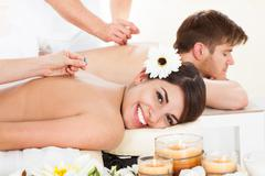 Portrait of happy woman undergoing acupuncture at beauty spa Stock Photos
