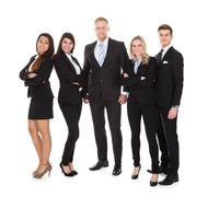 full length portrait of welldressed businesspeople standing against white bac - stock photo
