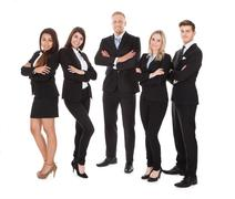 Full length portrait of welldressed businesspeople standing against white bac Stock Photos
