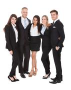 Full length portrait of welldressed businesspeople standing together against  Stock Photos