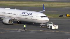 4K United Airlines airplane tow tug Stock Footage