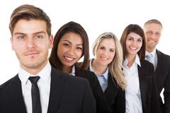 portrait of confident businesspeople standing in a row against white backgrou - stock photo
