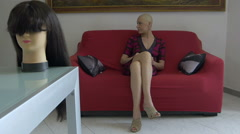 cancer survivor sitting on the couch: wig, loneliness, courage, faith, disease  - stock footage